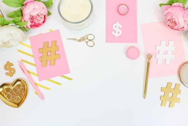 Op de foto is een flatlay met een aantal bloemen, een schaar, een kaars, wat papiertjes met daarop hashtags en een schaal met ringen.