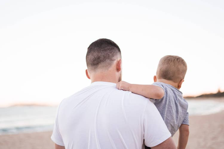 Op de foto staat een vader die zijn peuter vasthoudt. Op de achtergrond is er strand te zien.