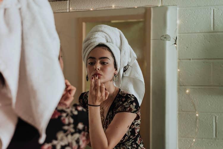 Op de foto staat een jonge vrouw voor de spiegel. Ze heeft een handdoek om haar haar. Ze kijkt in de spiegel en doet lippenbalsem op haar lippen met haar vingers. Ze draagt een shirt met bloemenpatroon. Rondom de spiegel hanger er kleine lampjes.