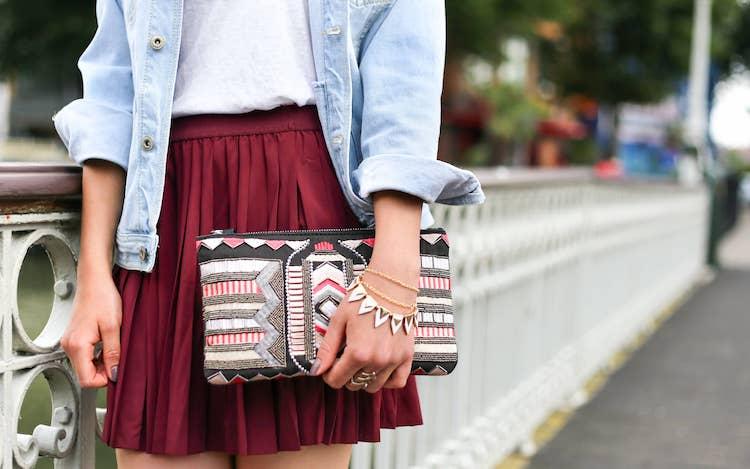 Op de foto staat een jonge vrouw met een jeansjasje en een korte rok. In haar hand houdt ze een kleine tas met een gestructureerd patroon. Ze heeft 3 armbandjes om haar arm en een grote ring. Ze leunt tegen een brug aan.