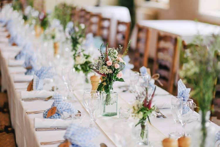 Op de foto staat een tafel met daarop een tafelkleed uit stof. De tafel is gedekt met bestek en glazen en in het midden staan bloemenvasen.