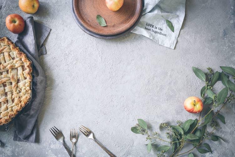 Op de foto staat een appeltaart, een bord met een appel erop en liggen er naast het bord een paar vorken.