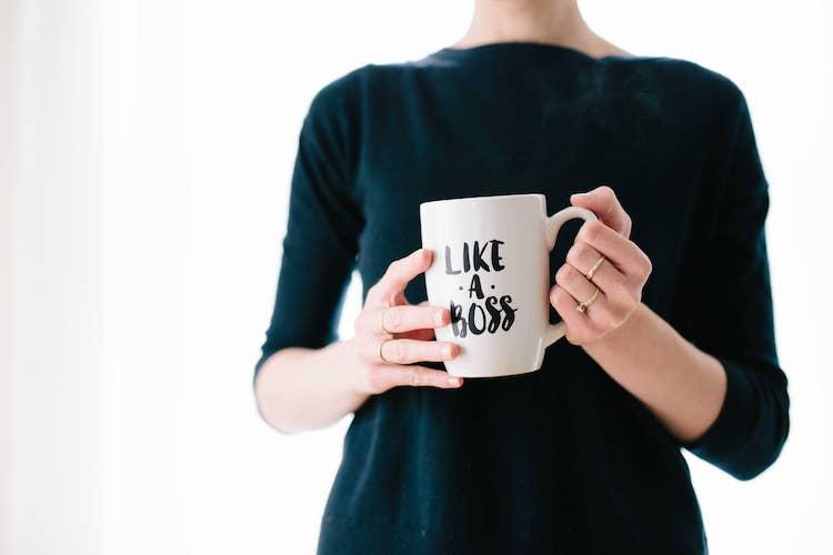 Op de foto staat een vrouw en ze houdt een mok in haar handen. Op de mok staat 'Like a boss'.