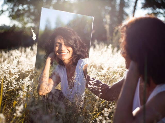 Op de foto staat een vrouw die een spiegel vasthoudt. Ze zit in een bloemenwei en glimlacht naar zichzelf in de spiegel. De vrouw heeft korte krullen en een shirtje aan. Het is een warme zomerdag.