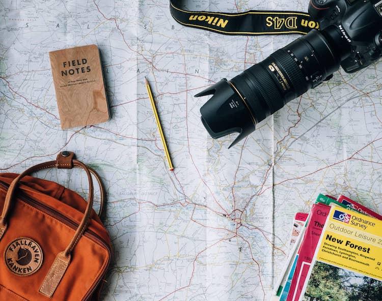 Op de foto staat een kaart met daarop een camera, een potloodje, reisboeken en een handtas.